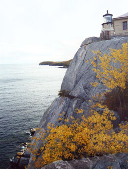 Split Rock lighthouse. It's not very tall but it doesn't need to be; perched atop a 170-foot granite cliff, it offers a commanding view of the lake. The keeper climbed the spiral stairs to light the kerosene burner for the first time in 1910, after a rash of serious shipwrecks on the rocks below. Ships' navigation compasses were rendered inaccurate by large masses of iron beneath the lake.